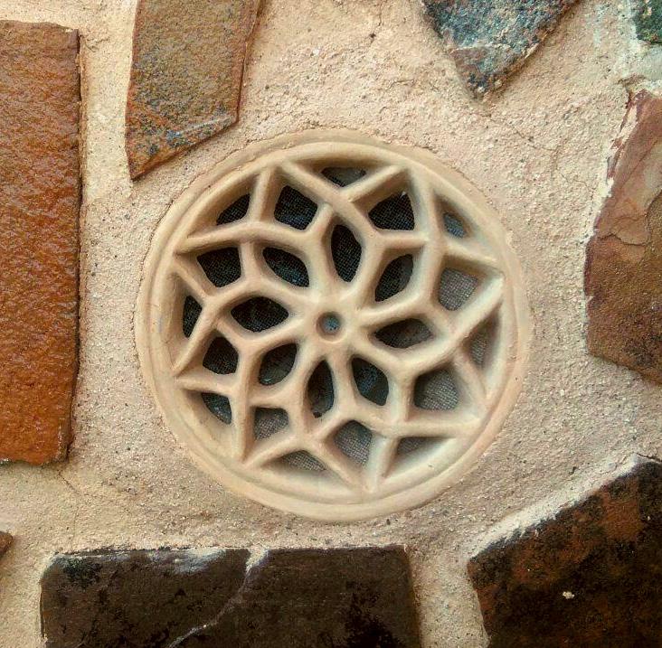 Rejilla de barro instalada en una fachada de piedra y cemento